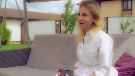 Adult blonde sitting on the porch swing at the backyard holding touch screen tablet in hands. Talk to somebody invisible with friendly smile. Caucasian young beautiful woman sways outdoors wearing in casual white shirt enjoy summer happy smiling. Stock Photo