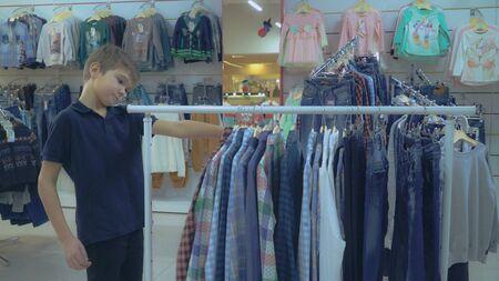 Young customer choose shirt in shop. Beautiful caucasian boy in shopping mall.