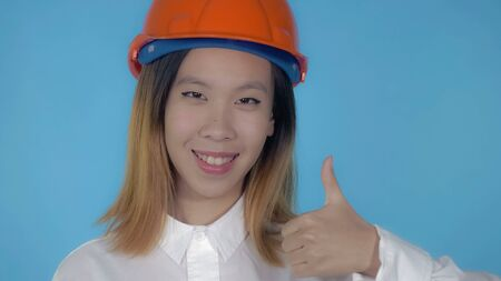close up portrait young asian architect wearing orange hard hat shows sign like on blue background in studio. attractive millennial girl looking at the camera