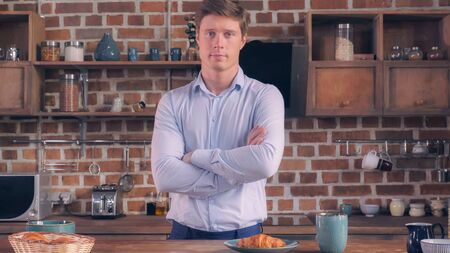 Young caucasian businessman posing looking at the camera in kitchen apartment. Handsome millennial man at breakfast time in flat.