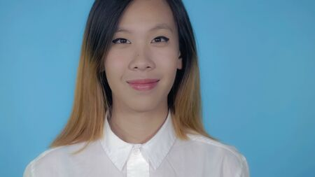close up portrait young asian woman on blue background in studio. attractive millennial girl looking at the camera Stock Photo