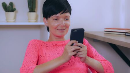 Portrait adult woman with happy friendly smile using smart phone. attractive female wearing colorful dress chatting with friend or use app on smartphone. cheerful girl with short haircut writing message on cellular indoors.