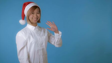 portrait young asian female posing wearing christmas hat waving hand say hello on blue background in studio. attractive korean woman with blond hair wearing white casual shirt looking at the camera smiling Stockfoto