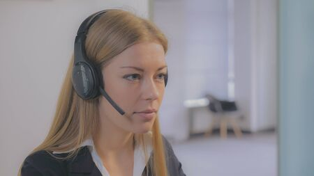 Portrait caucasian call center worker using headset talking with client or customer. Smiling caucasian woman consulting about services. Close up.