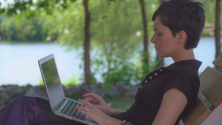 Portrait woman surfing internet or typing document or chatting in social net outdoors. On the background nature landscape with lake and green trees. Female with short black hair typing on computer.