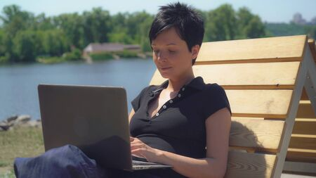 Businesswoman resting near river and using laptop. Adult happy woman typing on pc in summer season outdoors. Smiling caucasian model enjoy sunny day at the open air. Stockfoto