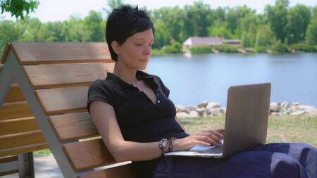 Portrait young caucasian brunette using laptop outdoors. Woman working on computer at the open air with beautiful view on nature and lake. Adult lady surfing internet or typing document in summer season.