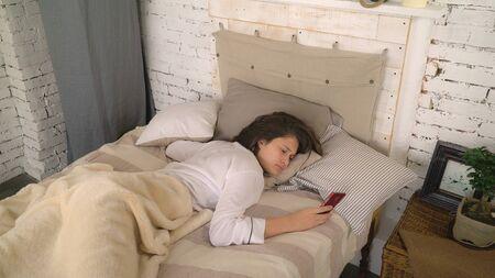 Morena con smartphone y siguió durmiendo. Mujer joven durmiendo en el dormitorio. Señora atractiva en ropa de dormir escondiendo el teléfono debajo de la almohada. Chica adulta acostada en la cama con ropa de dormir casual blanca. Foto de archivo
