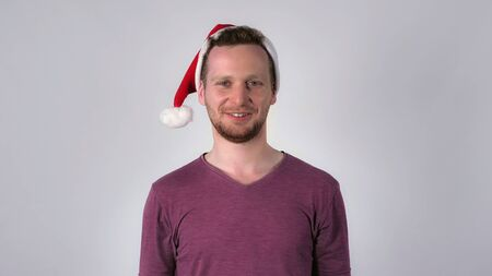 young caucasian man wearing santa hat for christmas looking at the camera with happy friendly smile. Portrait cheerful guy celebrating new year Stock Photo