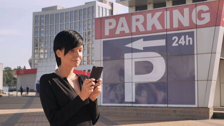 Businesswoman standing on the street near parking using smartphone. Adult woman texting or using application on mobile in city. Brunette with short hair wearing black dress on the background modern building.