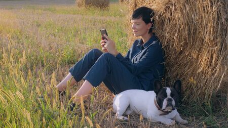 Young woman sitting at the meadow with french bulldog using smartphone. Attractive female wearing overalls texting message on mobile. harvesting in summer season.