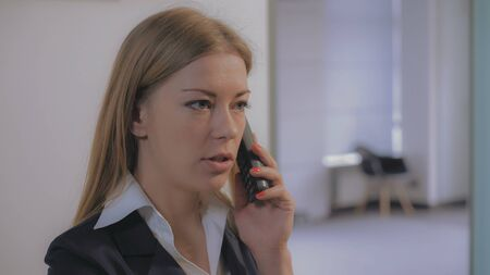 Beautiful professional woman with blond hair talking with client by phone. Smiling secretary or assistant appoint a meeting with partners. Caucasian model wearing in formal clothes. Stock Photo