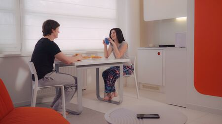 Young couple have breakfast at home. Smiling girlfriend and boyfriend enjoy free morning drinking coffee in small modern flat. Woman and man wearing in sleepwear.