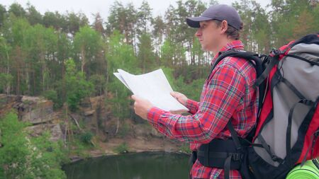 caucasian adult hiker looking around holding map checking road. Handsome man in mountain with lake view. Backpacker hiking spend holidays.