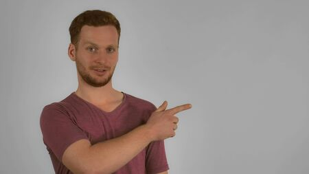 happy young casual man showing your products or text represents three points on grey background. redhead caucasian men with friendly smile pointing on one side Stock Photo