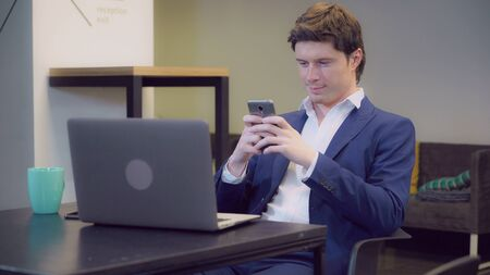 Caucasian young businessman waiting something or somebody in modern casual room play game on smartphone. Professional smiling guy wearing in elegant suit use application on smart phone.