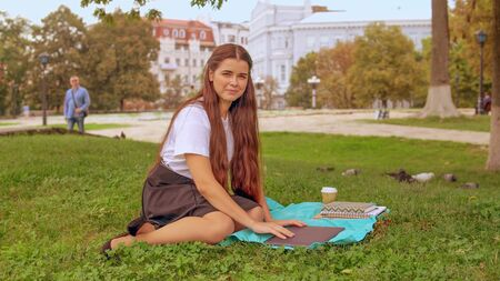 Young caucasian brunette with long hair sitting under the tree. happy student or businesswoman has break typing on laptop in city park