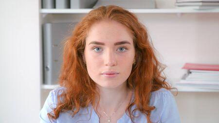 Portrait femme caucasienne aux cheveux roux bouclés regardant la caméra et souriant.