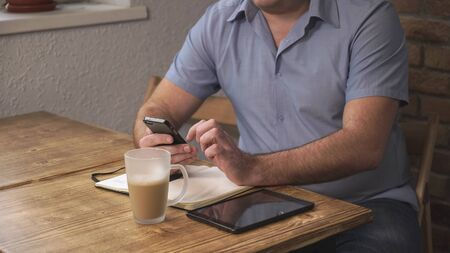 The man with the phone web surfing, manager of coffee breaks, is on the table and tablet notebook. Soft panorama