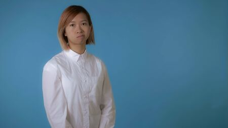 portrait young asian female posing showing hand gesture stopping crossing harms on blue background in studio. attractive korean woman with blond hair wearing white casual shirt looking at the camera 스톡 콘텐츠