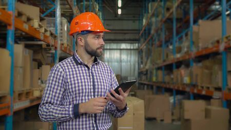 Manager working at warehouse. Handsome young man wearing casual shirt and hard hat using digital tablet entering data. Worker counting box for delivery.