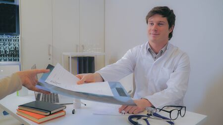 Caucasian doctor with friendly smile giving X-ray of the lungs patient. Professional man sitting in the office wearing in white coat. On the desk laptop, prescription and bottle with medicine Stock Photo