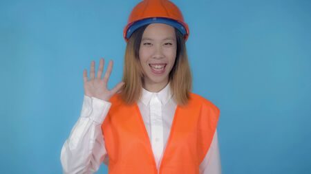 young asian woman posing on blue background in studio greeting viewers . attractive millennial girl wearing white casual shirt and orange hard hat and vest looking at the camera with cheerful happy smile