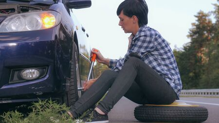 Young woman stuck on the side of the road with a flat tire. Caucasian brunette driver change a tire at the roadside.