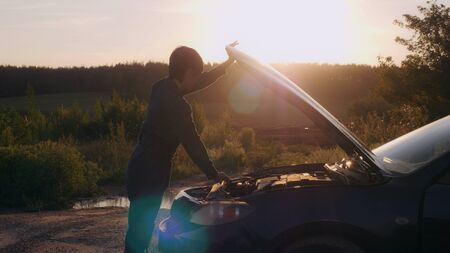 Woman mechanic opening car hood roadside in village. On the background beautiful forest in sunset.