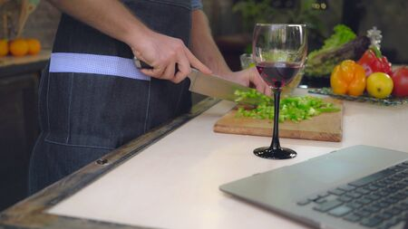 Close up details man cooking salad male hands cutting vegetables. On cook table wineglass and laptop