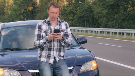 Young Caucasian man standing near broken car using app on smartphone chatting with customer service on the road. Male on the roadside texting message on cellular phone.