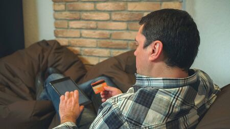 the man lie on the sofa and buy online. He holds in hands digital tablet and credit card