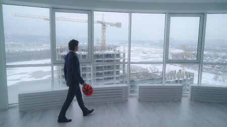 rear back view manager in real estate developer. employer in contemporary company looking through the windows in modern office on the construction site. urban landscape in winter season. man oversees building. Stock Photo
