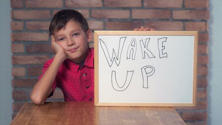 Portrait little boy showing whiteboard with handwriting word wake up. Child smiling and yawns. Preadolescent wearing in casual red shirt. Schoolboy with happy friendly smile. Stock Photo