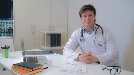 Portrait young caucasian doctor in the office. Handsome smiling man sitting at the desk with laptop and phonendoscope wearing in white coat. Md looking at the camera with friendly smile.
