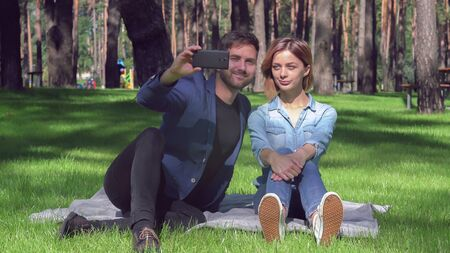 Tired woman and smiling man sitting on the grass take selfie photo at the park. Beautiful couple in love have fun on a date. Casual girlfriend and boyfriend in sunny summer day. Happy people wearing in casual denim shirt and jeans.