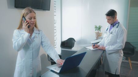 Doctor giving nurse patient s medical record. Adult professional therapist holding tablet fill documents using touch screen in clinic. Man wearing in white coat.