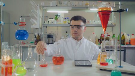 Handsome professional scientist holding flask. pouring liquid to glass bulb. Caucasian man wearing in white coat and eyeglasses working alone in lab. Фото со стока