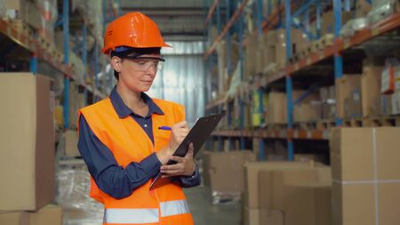 Woman worker standing near metal racks with boxes writing in paper document. Professional young employee in storehouse wearing uniform high visibility orange hard hat and vest.
