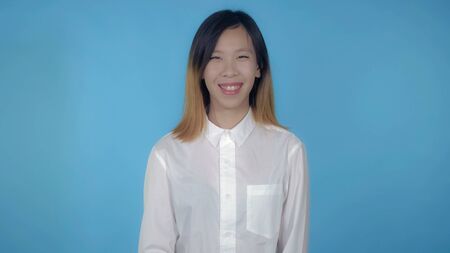 young asian happy woman posing showing positive emotions on blue background in studio. attractive millennial girl wearing white casual shirt looking at the camera smiling Stock Photo