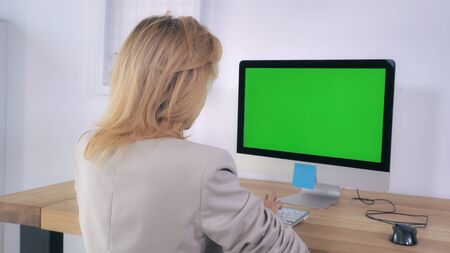 Blonde typing keyboard sitting at the working place with computer on the wooden desk display with green screen. Back view woman using pc in room with white wall