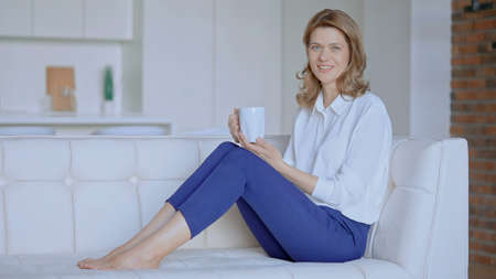 woman sits on the couch with a cup of coffee. High quality photo Archivio Fotografico