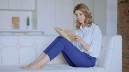 woman reads a book sitting on the couch. High quality photo