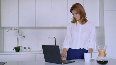 Businesswoman works in the kitchen with a laptop and drinks coffee. High quality photo
