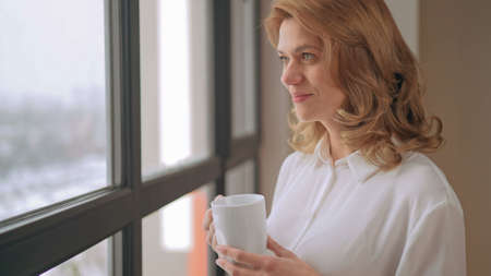Woman stands near window with a cup of tea. High quality photo