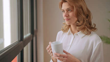 businesswoman stands near the window with a cup of coffee. High quality photo Archivio Fotografico