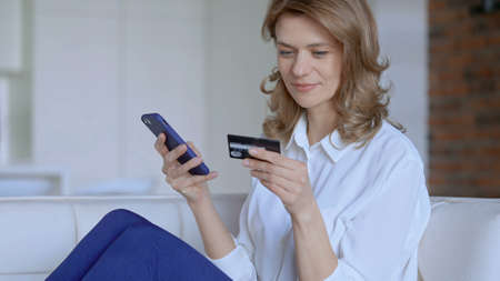 Woman sitting on couch buys online. High quality photo