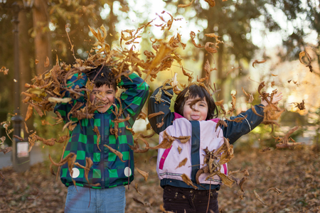 happy boy and girl throwing a bunch of leaves int heir had with amazing aoutumn ling and out of focus background