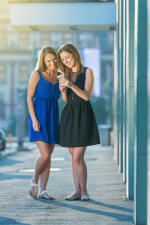 portrait mode of model female amazing brunette and blonde in the city cheking the phone and laughing in the sunligh of a beautiful city