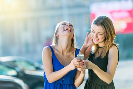 model female amazing brunette and blonde in the city cheking the phone and laughing in the sunligh of a beautiful city